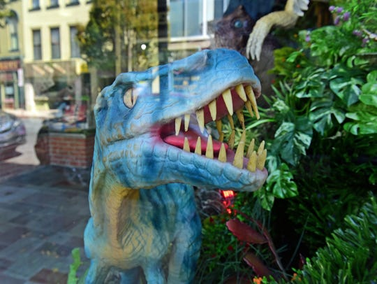 A dinosaur is in the display window at Toy Box Gifts