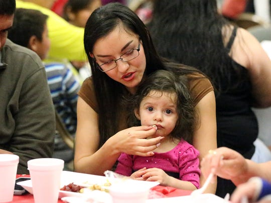 Lupita Villalobos feeds her 1-year-old daughter, Ailen Orozco Thursday at the El Paso Convention Center.