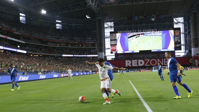 Mexico's Arlos Vela (11) shields the ball from Guatemala's Jose Contreras during a CONCACAF Gold Cup Group C match at University of Phoenix Stadium in Glendale July 12, 2015.
