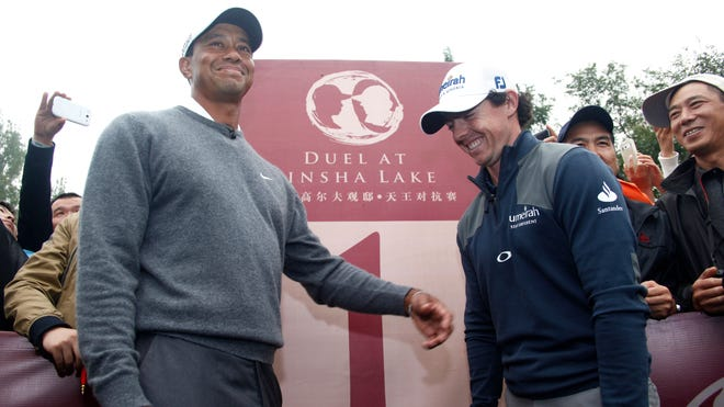 McIlroy shares a laugh with Tiger Woods before their 2012 match in China called the Duel at Kinsha Lake.