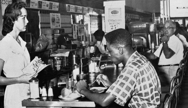 An unidentified man eats at a lunch counter in Tampa in 1960.  He is one of 70 who took part in breaking segregation barriers at 18 lunch counters in the city. They traveled from store to store, one or two at a time, and received service from white waitresses at counters previously reserved for white customers. No incidents were reported.