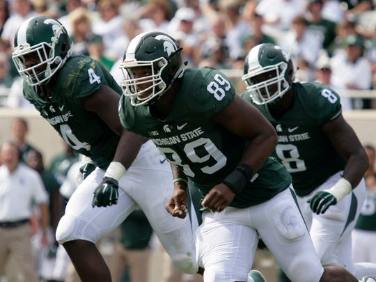 Michigan State's Shilique Calhoun (89), Malik McDowell (4) and Lawrence Thomas pursue the ball against Central Michigan.