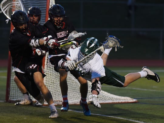 Ethan Plasker and  Kevin Griffith of Northern Highlands take down Andrew Robbins of Ramapo near the Northern Highlands goal in the first half.