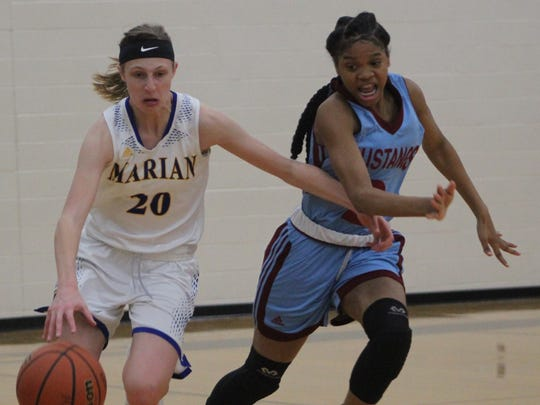 Marian's freshman guard Shannon Kennedy (20) attempts to elude Mumford's defensive pressure in Thursday's Operation Friendship championship game.