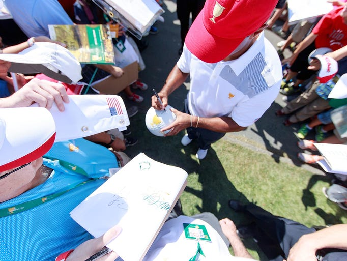 Tiger Woods of the U.S. Team signs autographs for fans during a practice round prior to the start of The Presidents Cup at Muirfield Village Golf Club.