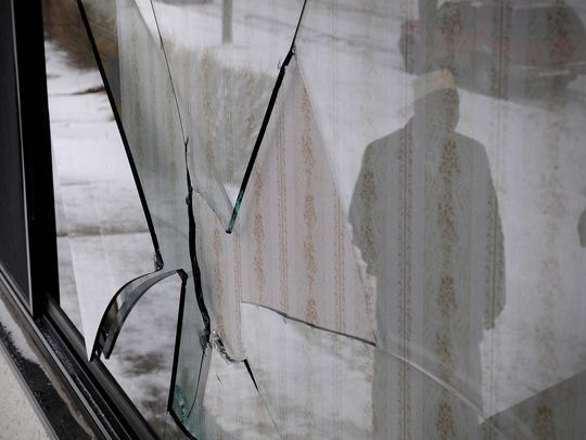 Imam Muhumed Ahmed looks at a window damaged in Dec.,