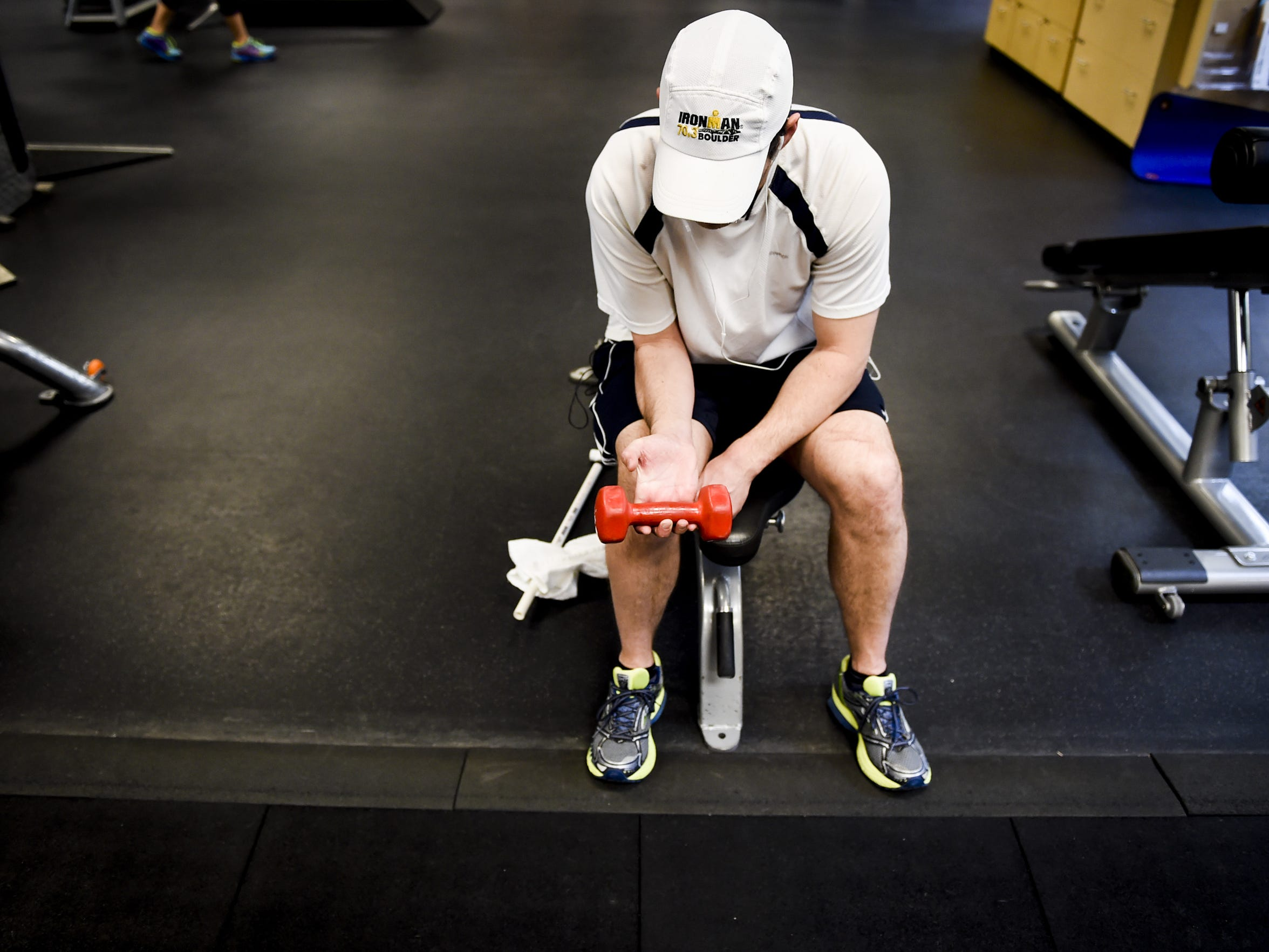 Holding a 5-pound weight, Jeff Wicks sits stretching