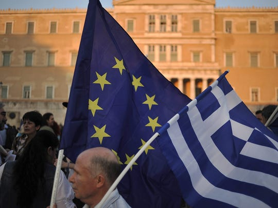 A demonstrator waves Greek and pro Euro flags during