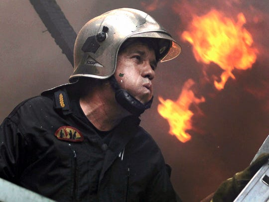 A fireman tries to extinguish a fire in the Karea suburb