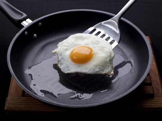 A fried egg is lifted out of a pan with a spatula.