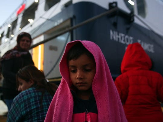 Refugees wait for transport after they arrived on the