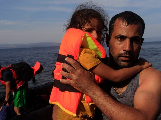 A man carries a little girl as refugees from Syria