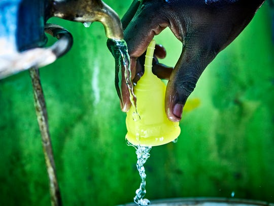 A woman washes a menstrual cup under a tap.