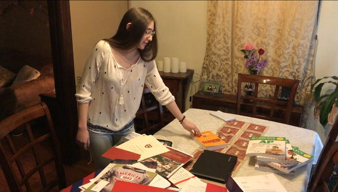 Catherine Sposato sifts through her many college acceptance packets and Adavnced Placement prep books.