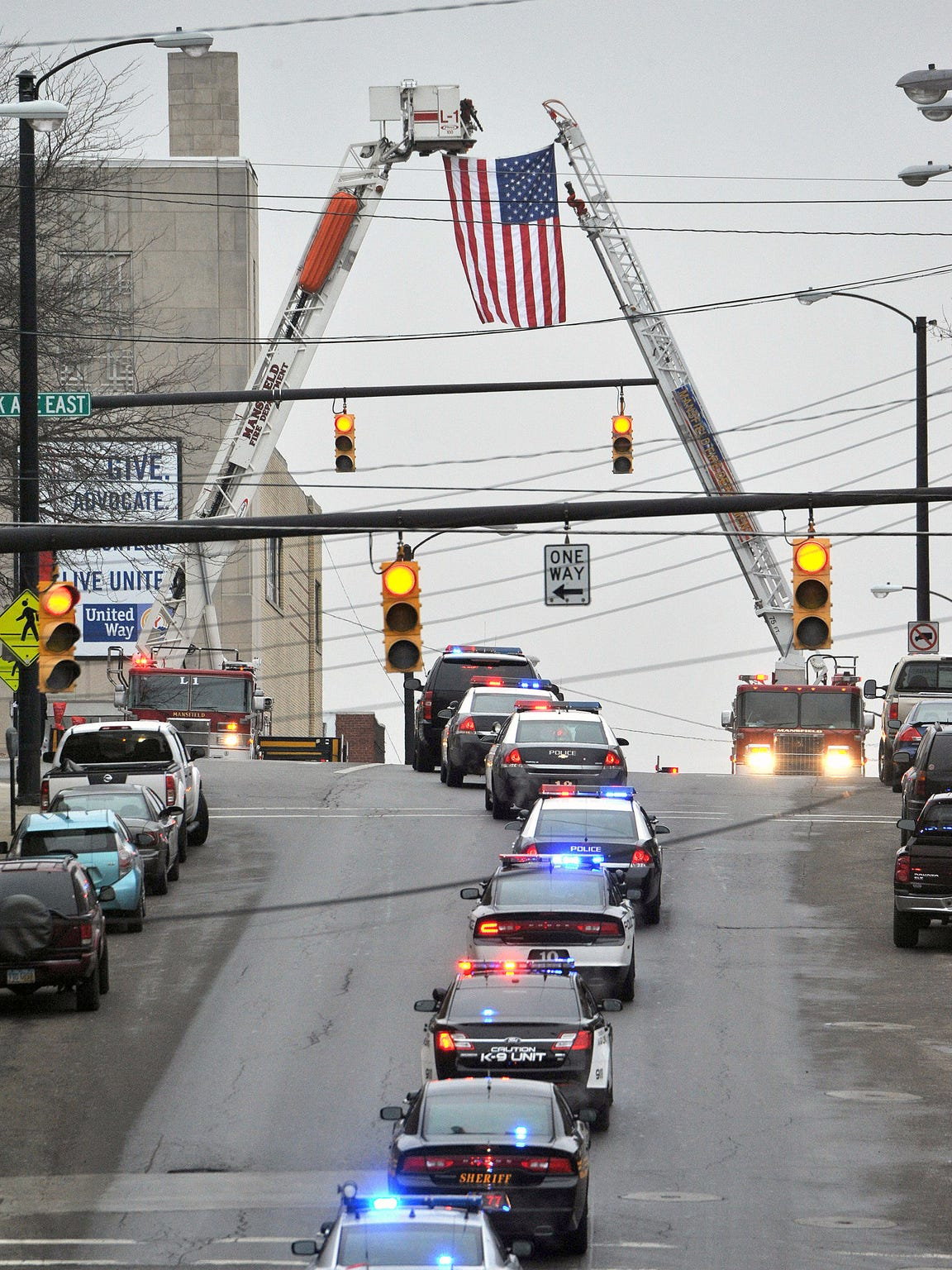 The Mansfield Fire Department hangs a flag at the intersection