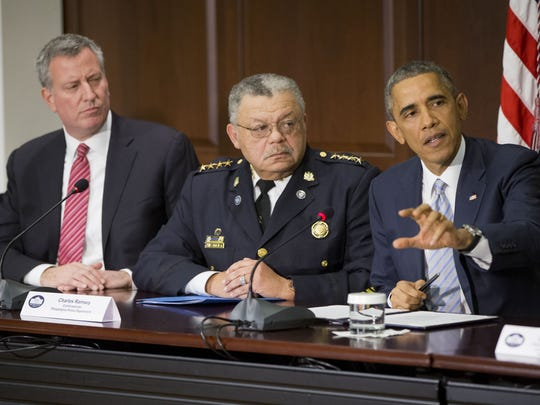 President Barack Obama, right, speaks during his meeting with elected officials, law enforcement officials and community and faith leaders in the Old Executive Office Building on the White House Complex in Washington, Monday, Dec. 1, 2014. Also at the meeting are New York Mayor Bill de Blasio, left, and Charles Ramsey, center, Commissioner of the Philadelphia Police Dept.