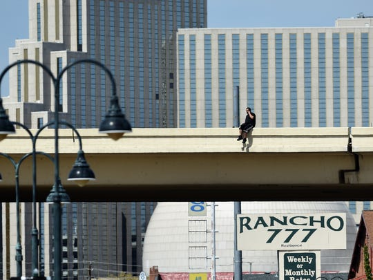 People gather on Fourth Street as they watch a man sitting on the edge of the Wells Avenue overpass Friday morning on May 4, 2018. Reno police blocked traffic on both sides of the street.