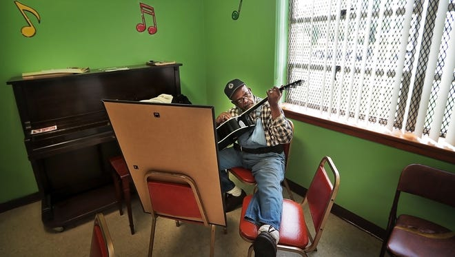 """C.W. Ayers Jr., 67, practices guitar scales in the music room at the Josephine K. Lewis Senior Center Tuesday afternoon. """"Looking for that wolf G-sound,"""" Ayers said. The Lewis Center and other Parks and Recreation facilities are a priority in this year's budget along with a bump for MPD and street paving."""