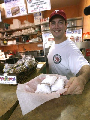 In this 2008 photo, Don Applebaum offers up beignets at Cajun's Kate, a New Orleans-style eatery in Booths Corner Farmers Market in Boothwyn, Pa.