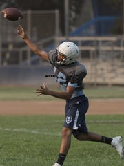 Quarterback Frankie Ayon passes during Redwood football