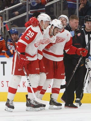Red Wings defenseman Ryan Sproul (48) is helped off the ice by teammates Anthony Mantha (39) and Xavier Ouellet (61) during the second period of the Wings' 4-3 loss Saturday in Edmonton, Alberta.