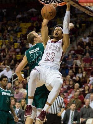 New Mexico State's Eli Chuha powers in a dunk against Utah Valley's Isaac Neilson Saturday at the Pan American Center.
