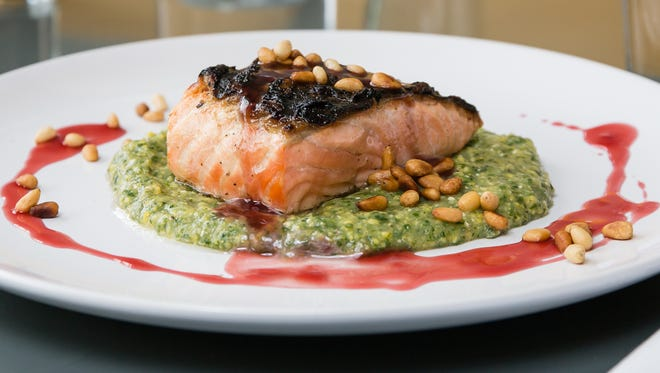 Salmon with kale polenta, pomegranate reduction and toasted pine nuts