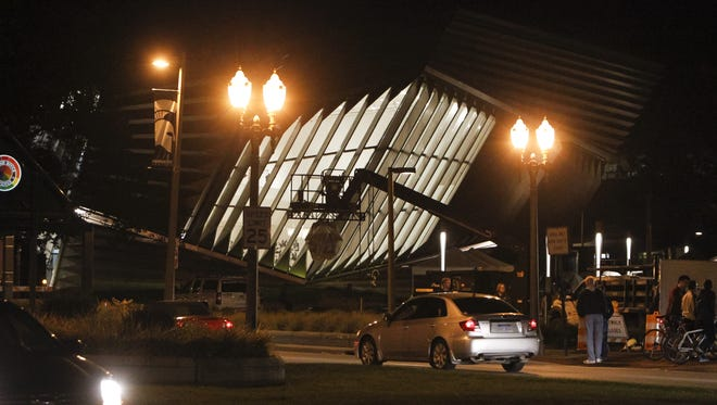 A few people mill outside the closed set of the film 'Batman v Superman' Wednesday evening, October 15, 2014, on the south side of the Eli Broad Museum in East Lansing.  [Photo by MATTHEW DAE SMITH | for the Lansing State Journal]