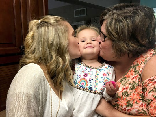 Kennedy Griest, left, and her mother, Wendy Andrews, each plant a kiss on 2-and-a-half-year-old Adalyn at the family's Green Oak Township home.
