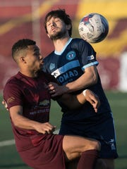 Detroit City FC forward Roddy Green goes for the ball against the Milwaukee Torrent midfielder Tony Patterson during the first half Friday, May 12, 2017 at Keyworth Stadium in Hamtramck.