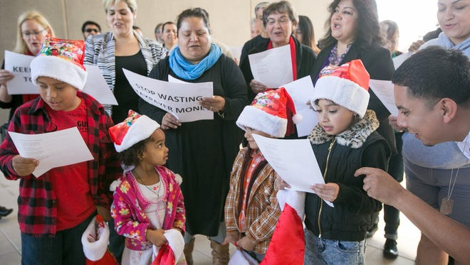 A coalition of Arizona immigrant-rights groups sing carols outside the Maricopa County Sheriff's Office in Phoenix on Monday, Dec. 22. The groups were protesting a lawsuit brought by Maricopa County Sheriff Joe Arpaio against the Obama administration.