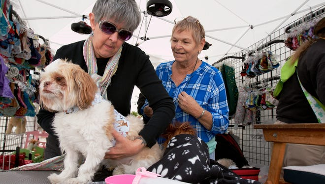 """Pam Vanneman of Pozy?s Closet, left, fits Smokey, a Shih Tzu owned by Beverly Girard of Cape Coral, with a harness vest. Pam Vanneman, of Pozy's Closet, left, fits """"Smokey"""" a three year old Shih Tzu, with a harness vest as Smokey's owner, Beverly Girard, of Cape Coral, watches during The Cape Coral Festival of the Arts on Saturday, Jan. 10. The booth featured hand crafted harness vests and sling carriers for dogs in multiple patterns. The Cape Coral Festival of the Arts is celebrating it's 30th year, and features the work of more than 300 artists featuring fine art, sculpture, pottery, jewelry, photography, metal works, and mixed media."""