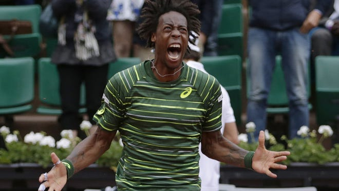 France's Gael Monfils celebrates after winning his match against Uruguay's Pablo Cuevas during the men's third round of the Roland Garros 2015 French Tennis Open in Paris on May 29, 2015.