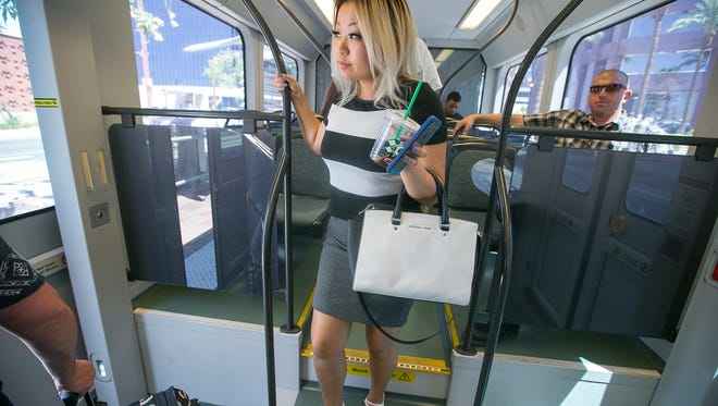 Commuter Lynnie Nguyen exits a light-rail train in Phoenix on Monday, Aug. 3, 2015.