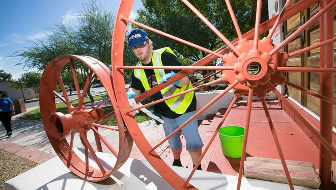 Chris Knox wipes down a hand rail outside the Peoria Arizona Historical Society museum on Wednesday, October 7, 2015 as part of the Group Supported Employment program, which gives jobs to disabled adults in Peoria.