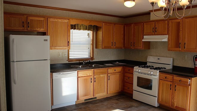 These mobile homes come with full kitchens that have white appliances and oak cabinets.