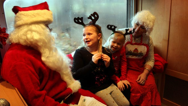 """Anna Turton (7) and her sister Libby (5), from Liverpool, make the most of their visit with Santa. Anna had prepared """"a whole list."""""""