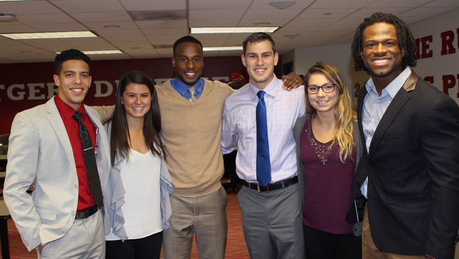 Rutgers assistant athletics director Shawn Tucker (center, beige shirt) is in charge of the Rutgers Leadership Academy, formed to help athletes like the ones pictured with him succeed after their playing careers end.
