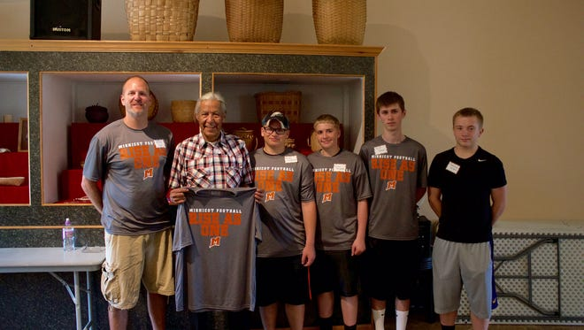 Several members of the Mishicot High School football team and coach Kevin Fix present Earl Meshigaud, great grandson of Chief Mishicott, with a commemorative Mishicot football t-shirt.