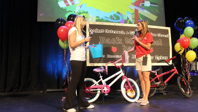Project Outreach representative Cassie Dalton and Life Christian Church Pastor Tracy Boyd announce bike raffle winners during the 2015 Back to School Bash.