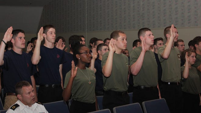 The high school military recruits repeat the Oath of Enlistment.