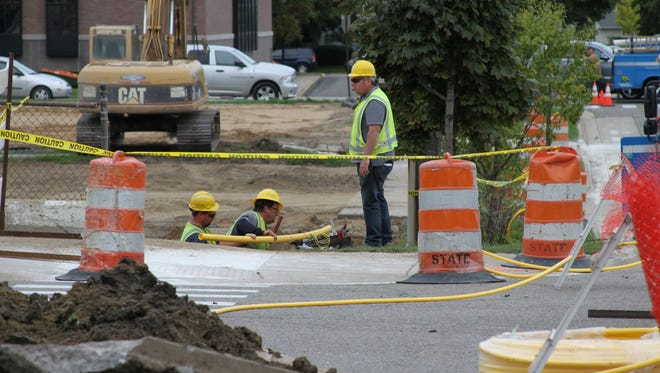 A Consumers Energy crew works to replace a portion of a 2-inch gas main that was severed on Wednesday by a construction crew renovating a parking lot on Clinton Road.