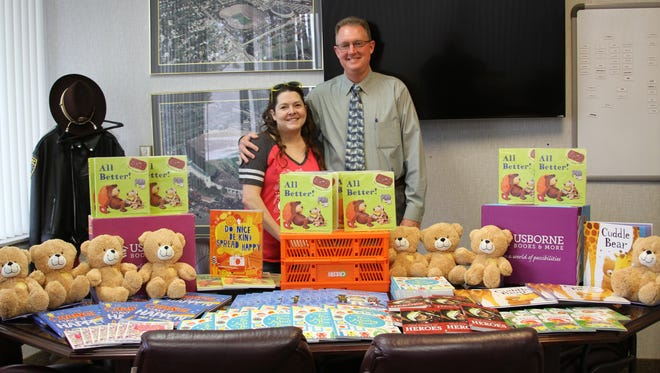 Lauren Moore, left, team leader with Usborne Books & Moore, donated just under 100 books and numerous teddy bears to the Livingston County Sheriff's Department in September. The books were donated by six people during a book drive.