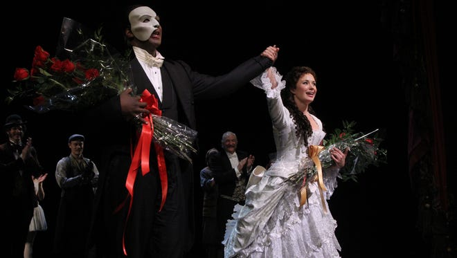 This May 12, 2014 photo released by The Publicity Office shows Norm Lewis, left, and Sierra Boggess acknowledging applause on the pair's opening night with the Broadway production of The Phantom of the Opera at The Majestic Theatre, in New York.