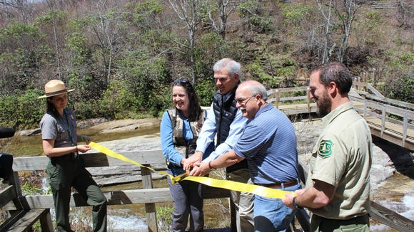 Caitlin Worth, Executive Assistant at Blue Ridge Parkway, Carolyn Ward CEO Blue Ridge Parkway Foundation, John Cottingham executive director of Pisgah Conservancy, Phil Francis Former Blue Ridge Parkway Superintendent, and Dave Casey, Pisgah District Ranger, cut a ribbon at Graveyard Fields April 25.