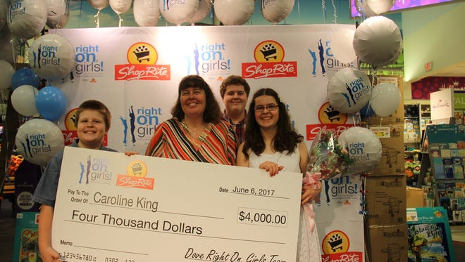 Caroline King, 17, of Newark, is joined by her mother and brothers as she holds her oversized scholarship check from ShopRite and Dove. She was one of four girls recognized by ShopRite and Dove as Dove Right on Girls Scholarship winners for giving their talent and time to their respective communities.