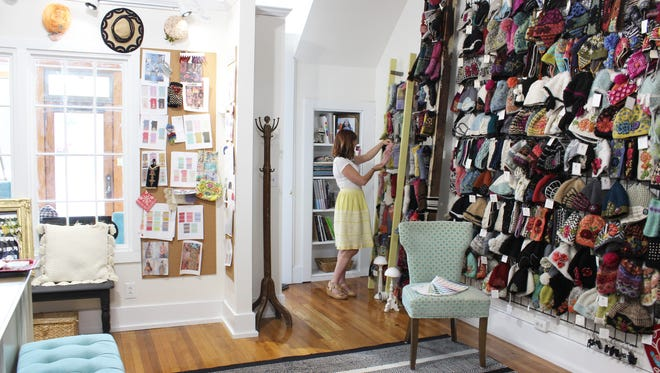 Lindsay Mason, owner at French Knot, arranges a display at her Main Street office.