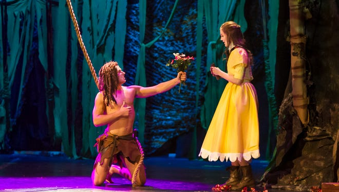 """Tarzan (Bryson Petersen) presents Jane (Ashlen Loskot) a handful of fresh flowers in the Wichita Theatre's production of """"Tarzan: The Musical."""" The play runs through Feb. 24, with shows on Friday and Saturday nights, matinees on Saturdays."""