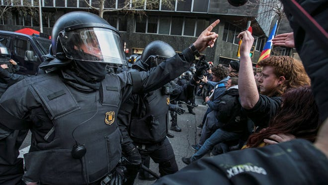 Catalonian riot police and protesters clash during a protest against the detention of former Catalan leader Carles Puigdemont at the Spanish Government Delegation in Barcelona, in northeastern Spain on March 25, 2018.