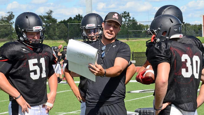 Pinckney assistant coach Cody Patton goes over details of a blocking assignment with Caudy Hendee, left, and Levi Collins.
